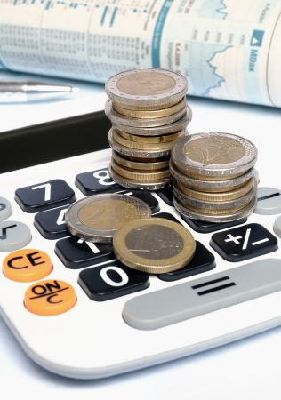 Calculator with Euro coins, ball pen and stock market report on white background photo