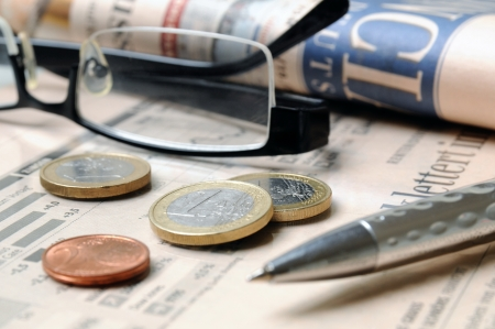 fx: Euro coins, glasses and ball on top of a financial report