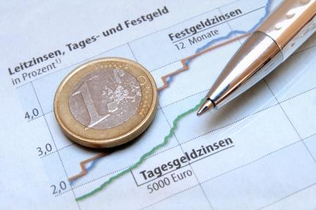 perdidas y ganancias: Monedas de euro y un bolígrafo en un gráfico de inversión de dinero de color azul claro Foto de archivo