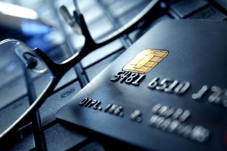 黒のクレジット カードとラップトップ上の眼鏡