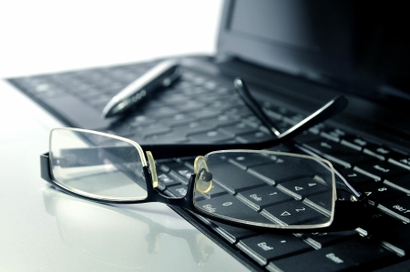 ball pen: Glasses and ball pen on top of a laptop Stock Photo