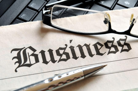 Business, glasses and ball pen on newspaper headline  photo