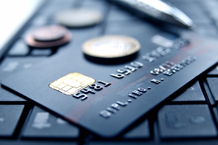 creditcard: Credit card and money coins on a laptop