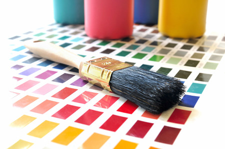 Wooden paintbrush on a color guide with paint tubes in background photo
