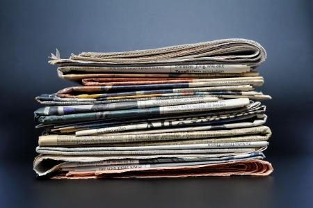 news flash: Pile of newspapers on black background  Stock Photo