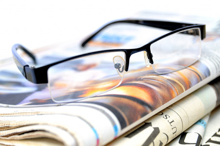 breaking news: Stack of newspapers with glasses on top