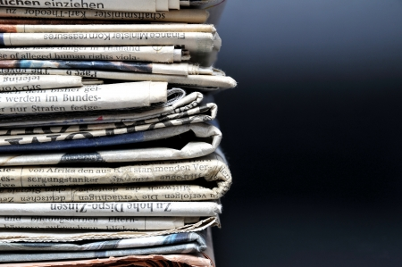 Stack of newspapers on black background  photo
