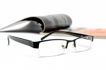 Magazine with glasses on white background  photo
