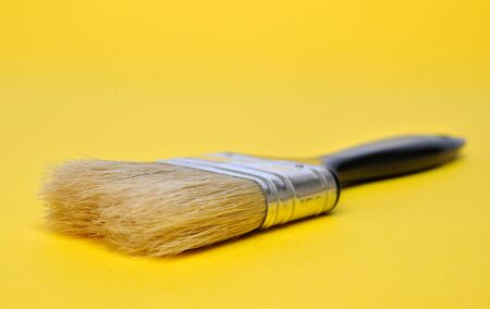 Black paint brush on yellow  photo