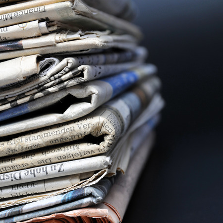 Stack of newspapers on black background