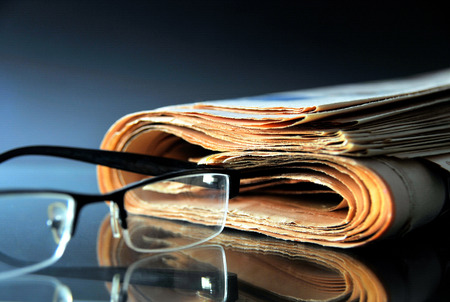 Rolled up newspaper with glasses Stock Photo