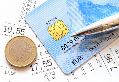 credit union: Credit Card and Euro coin on top of supermarket receipts  Stock Photo