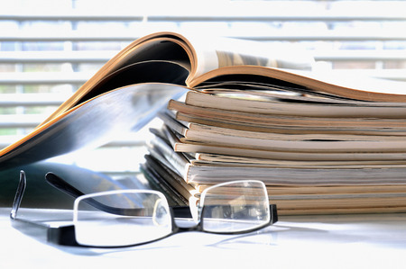office politics: Stack of magazines with black glasses
