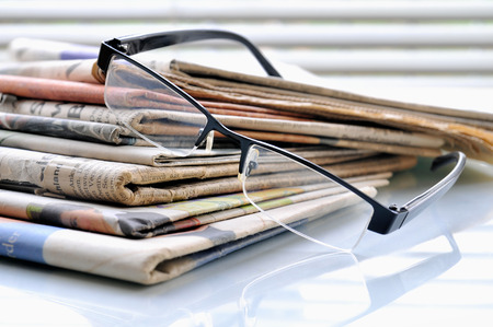 Stack of newspapers on office desk with glasses