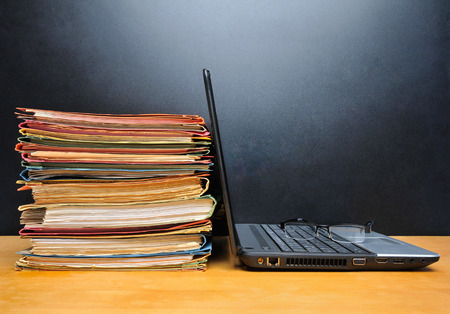 Laptop and office files on wooden table in front of black wall  photo