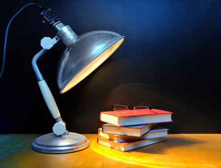Small stack of books with glasses and vintage lamp in front of black wall photo