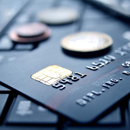 Zwarte creditcard op computer toetsenbord met geld munten