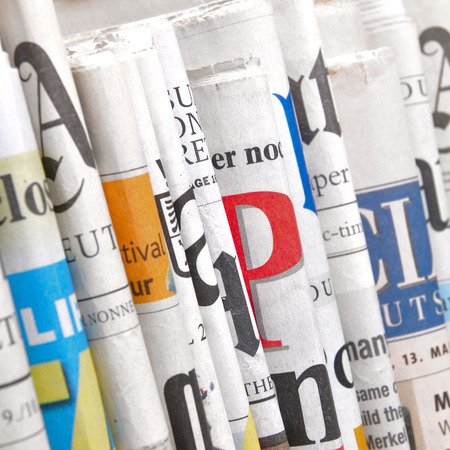 Row of folded newspapers Stock Photo
