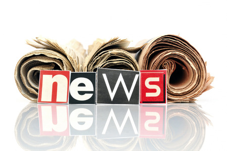 Three rolled newspapers with lettering in front NEWS