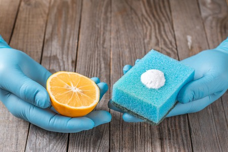 sodium bicarbonate: cleaning tools and sodium bicarbonate in hand on wooden table Stock Photo