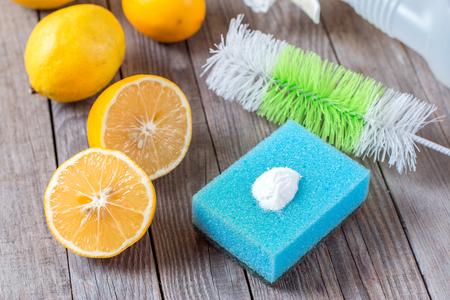 Eco-vriendelijke natuurlijke reinigingsmiddelen baking soda, citroen en doek op houten tafel Homemade green cleaning