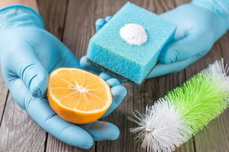 bicarbonate: Eco-friendly natural cleaners baking soda, lemon and cloth on wooden table in hand Stock Photo