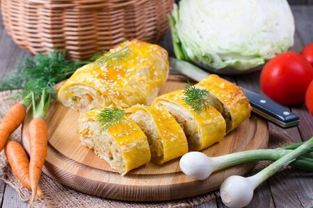 Roll with cabbage on a wooden board