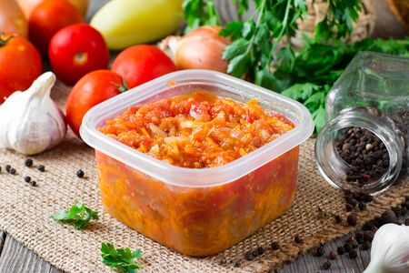 Stewed carrots and onions in a plastic container