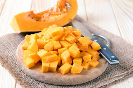 vitamine: Cubes of pumpkin on cutting board and knife on wooden table