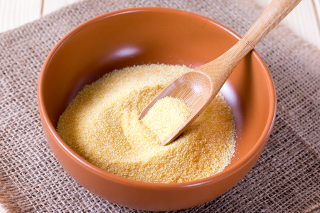 Semolina in a bowl with a wooden spatula Stock Photo