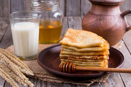 Thin pancakes on a plate with honey and a glass of milk on a wooden background. Tasty breakfast