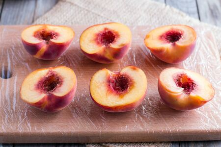 white washed: Cutting peaches in half for making grilled peaches Stock Photo