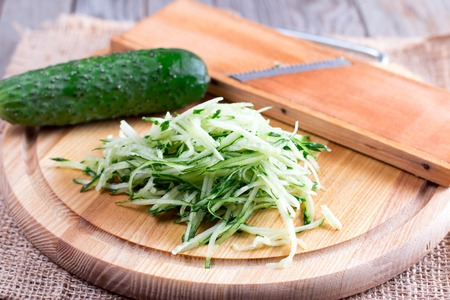 Green cucumber grated on wooden board