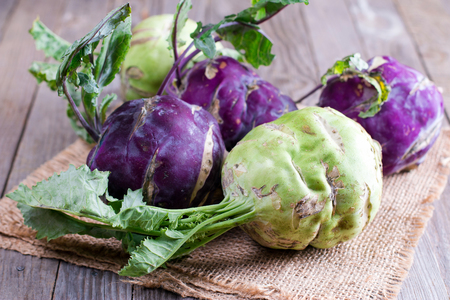 Kohlrabi cabbage with green leaves on wooden background Stock Photo