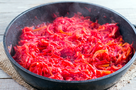 roasting pan: Carrots, beets and onion in a frying pan are roasted on the stove. Ingredients for borsch