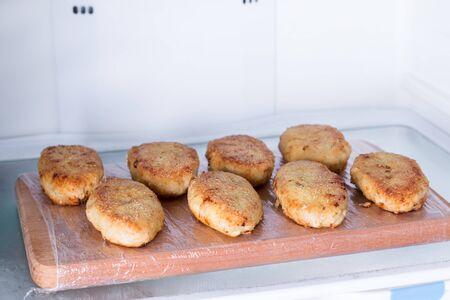 Cutlets on a wooden board in the fridge