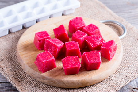 Frozen berry cubes on a cutting board