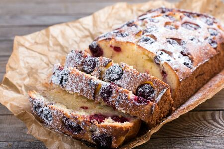 Slice of homemade cranberry cake with cherries and powdered sugar