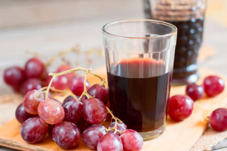 Grapes and a glass of wine on a wooden table