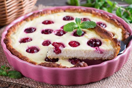 A piece of a pie (cheesecake) with cherry filling on wooden table