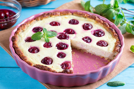 Cherry open pie with cottage cheese and sour cream filling, in baking form on wooden table