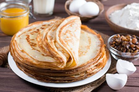 Many pancakes on a wooden background. Traditional Ukrainian or Russian pancakes. Shrovetide Maslenitsa. Traditional dishes on the holiday Carnival Maslenitsa Shrovetide.