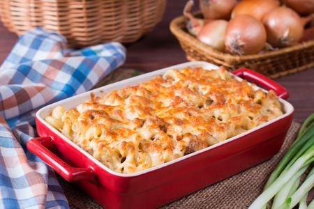 Pasta casserole with cheese and ham with tomato and cream sauce. Macaroni and cheese