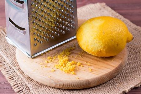 Cut lemon and zest on wooden board, closeup