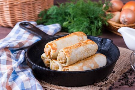 Crepes stuffed with minced meat and rice in a frying pan on a table Stock Photo