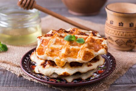 Tasty waffles with honey on plate on the table Stockfoto