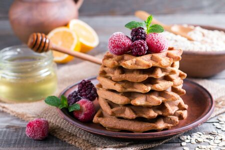 Fresh homemade waffles with berries and honey for breakfast on wooden background.