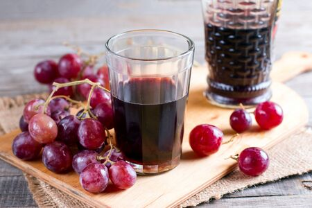 Red wine in a glass with grapes on an old table