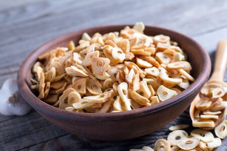 Bowl with dried garlic flakes on wooden table