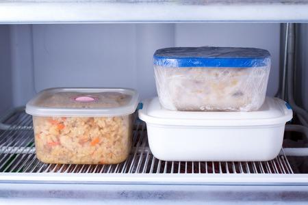 Alimentos congelados en un recipiente en el congelador. Nevera con alimentos congelados. Comida lista Foto de archivo - 97657890
